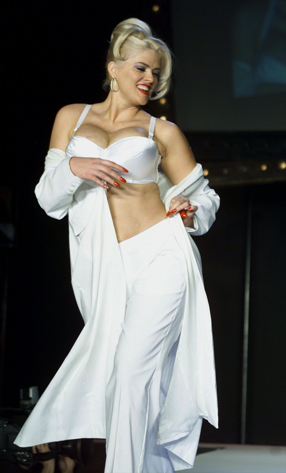 Anna Nicole Smith wears a long coat with pants as she models at the Lane Bryant fashion show Februar..