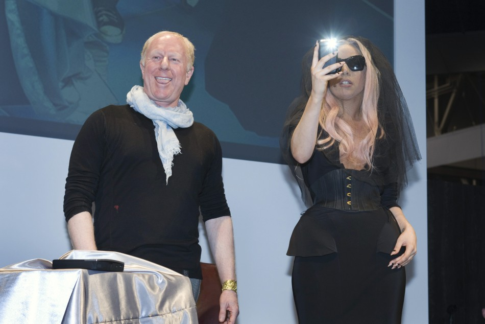 Polaroid Chairman Sager smiles as singer Lady Gaga takes a photo with her mobile phone