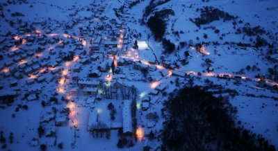 An aerial view of the small eastern city of Kalinovik covered by snow during winter at night