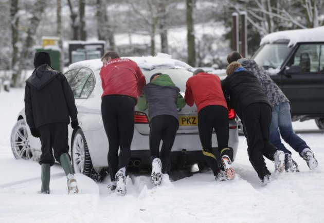 Passing runners help push a stranded car stuck in the ice and snow in Newtown Linford, Leicstershire