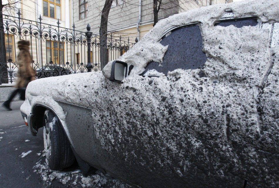 A woman passes by a car, covered with snow and dirt, during winter in central Moscow