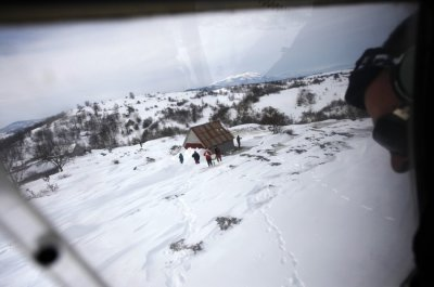 A helicopter pilot tries to land during an emergency evacuation in the isolated village of Donji Drezen during winter in eastern Bosnia