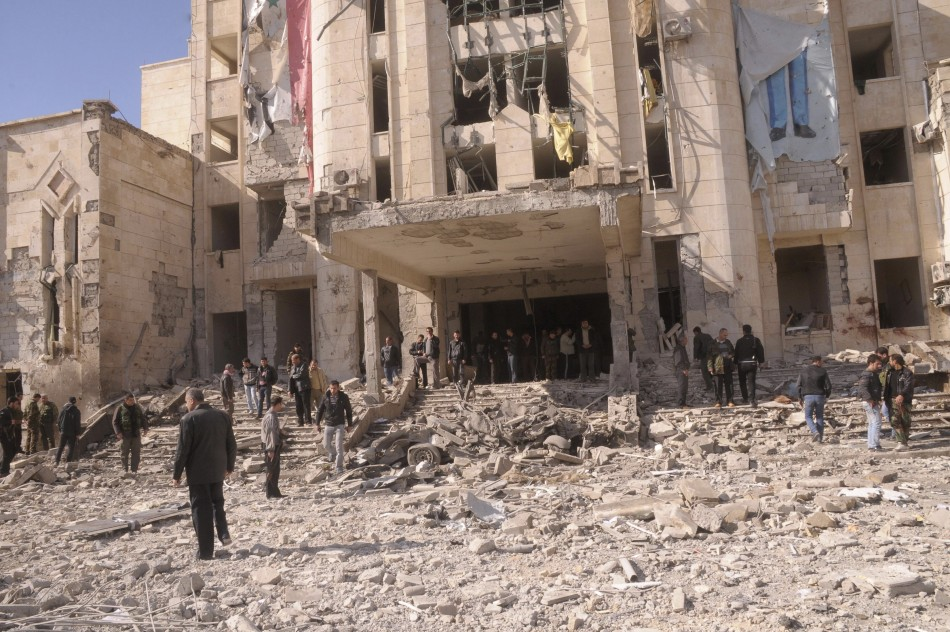 Syrian security personnel inspect the site of an explosion in Syria's northern city of Aleppo