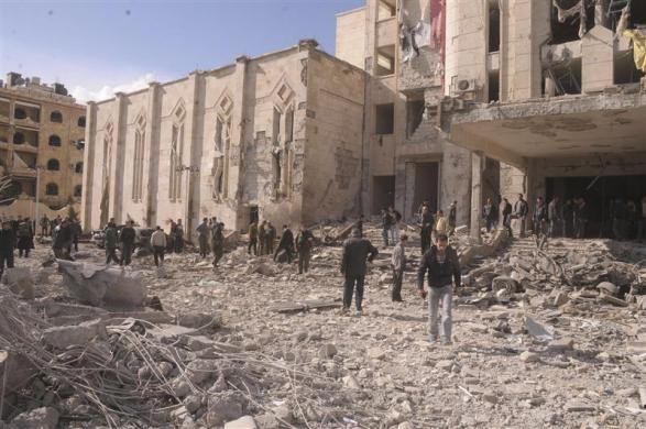 Syrian workers inspect the site of an explosion