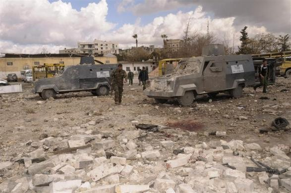 Syrian security personnel inspect damaged riot police vehicles