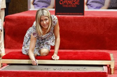 Aniston signs her name in cement during a hand and footprint ceremony at the Graumans Chinese Theatre in Hollywood