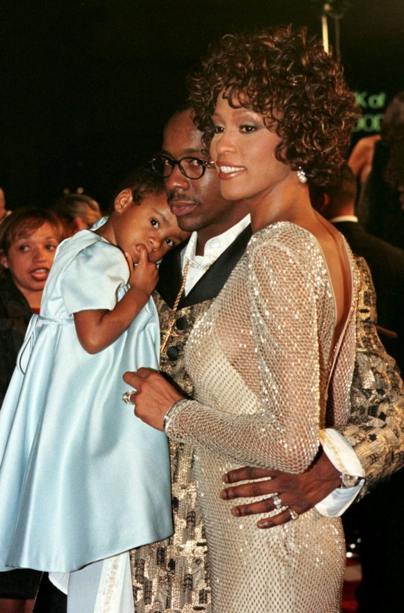 Whitney Houston and Bobby Brown posing with a young Bobbi Kristina