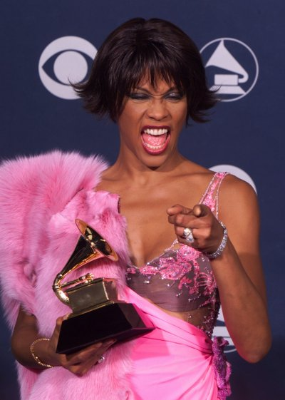 SINGER WHITNEY HOUSTON POSES WITH GRAMMY AWARD.