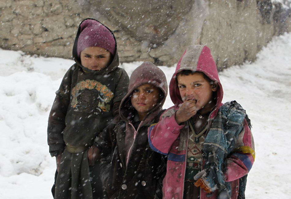 Afghan children pose for a photo as they stand in the snow outside their shelter at a refugee camp in Kabul