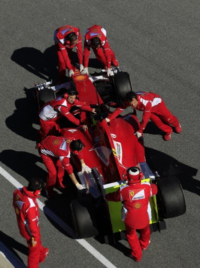 Ferrari F1 driver Massa of Brazil sits inside his 663 as team members push his car into the garage in Jerez