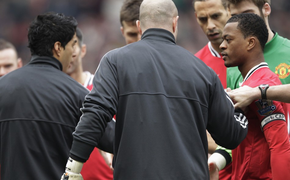 Manchester United's Evra reacts after Liverpool's Suarez ignored his handshake before their English Premier League soccer match in Manchester