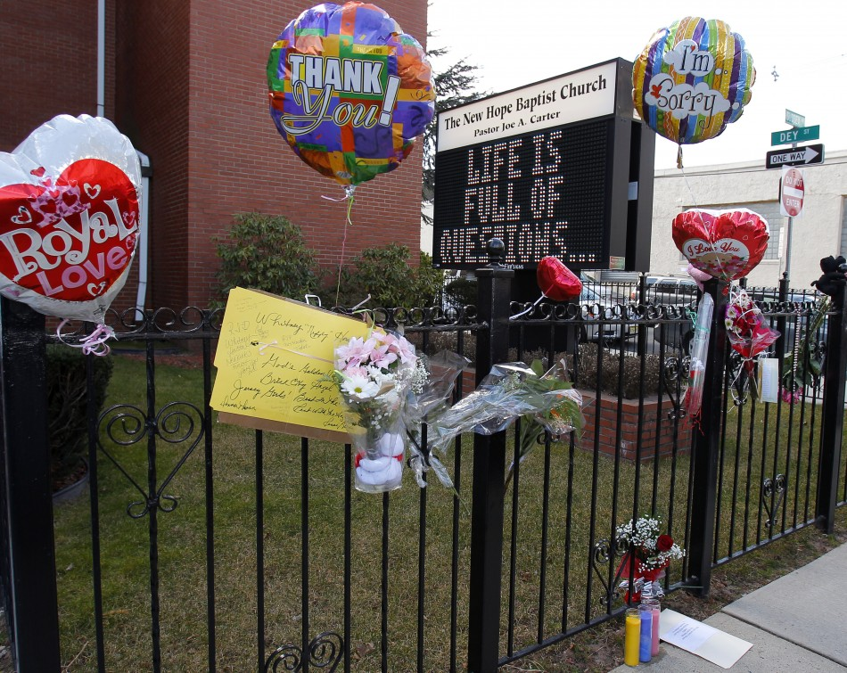 Flowers and a card are seen at a makeshift memorial in front of The New Hope Baptist Church in Newark