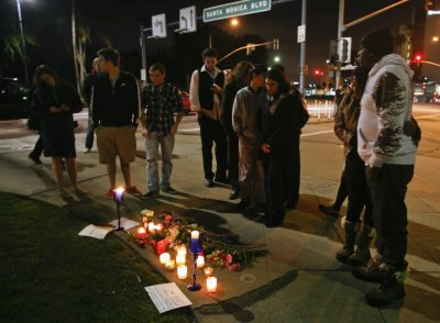 People gather at makeshift memorial on corner of Santa Monica and Wilshire Boulevard to mourn death of singer Whitney Houston in Beverly Hills