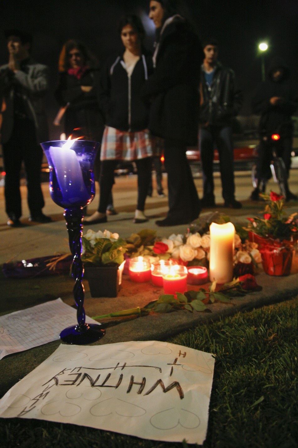 Mourners gather at a makeshift memorial on the corner of Santa Monica and Wilshire Boulevards as they mourn the death of singer Whitney Houston in Beverly Hills, California