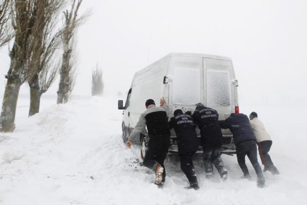 Men push van stalled on road during heavy snowfall near Glodeanu Silistea village in Romania