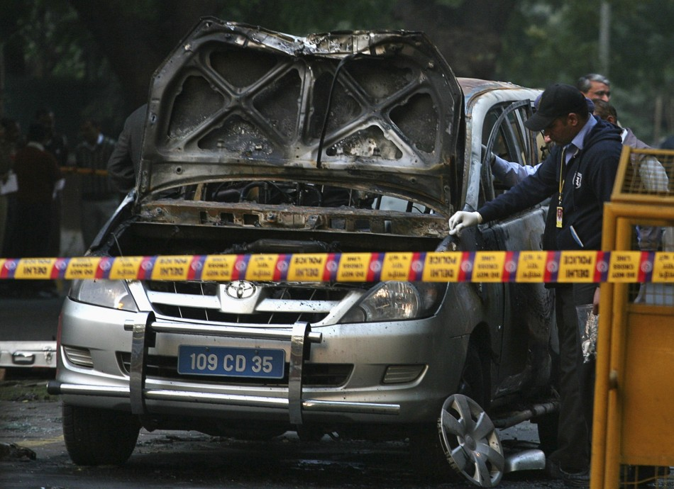 Police and forensic officials examine damaged car at Israeli Embassy after explosion in New Delhi