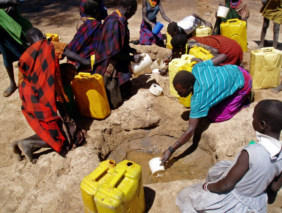 gandan women and children collect water from a hole dug in a dry riverbed at Kaabong village, Karamoja region