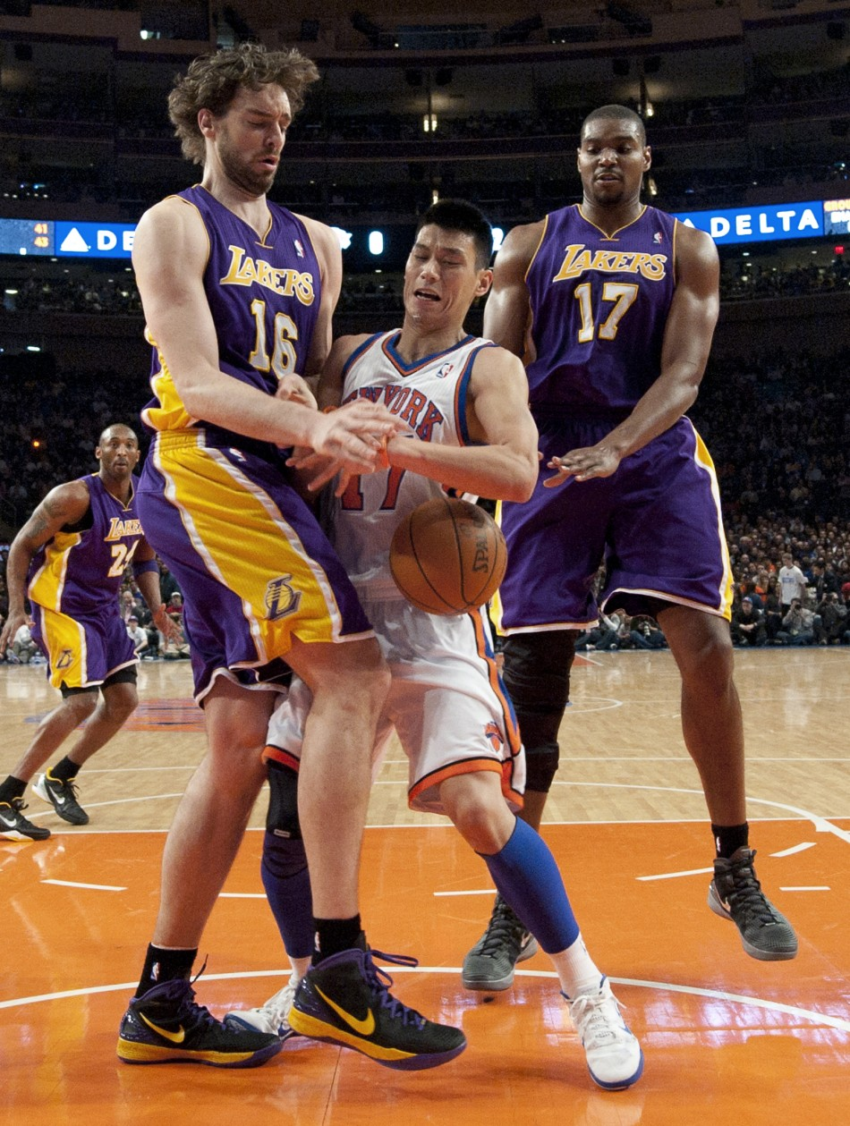 Los Angeles Lakers Pau Gasol and center Andrew Bynum force New York Knicks Jeremy Lin to lose ball in NBA game in New York
