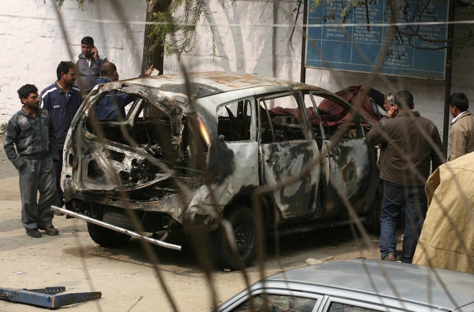 Police cover the damaged Israeli embassy car in New Delhi