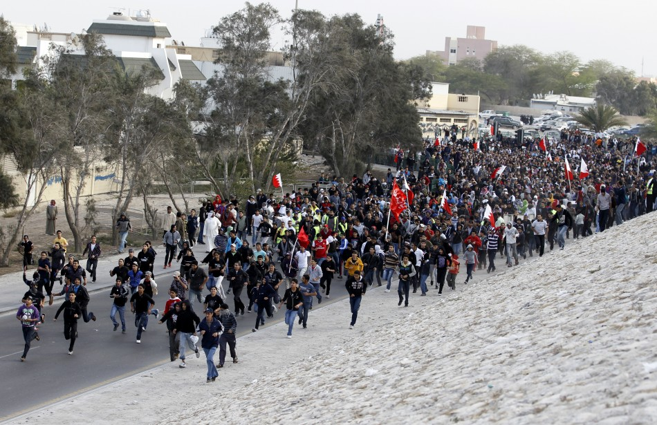 Pro-democracy  protesters run towards Farooq Junction during protest in Manama