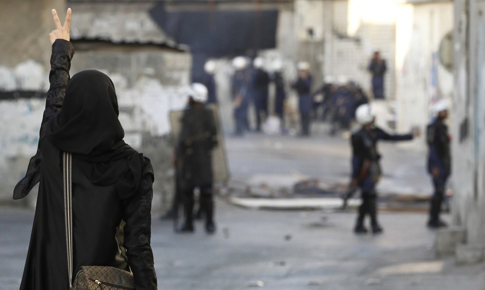 A protester shows a victory sign to riot police during clashes in Bahrain