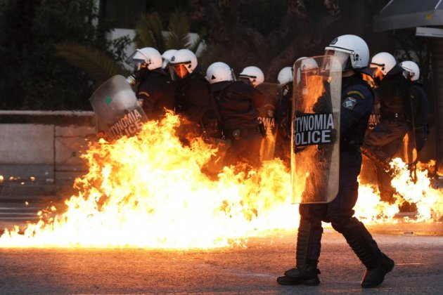 Petrol bomb explodes near riot police during huge anti-austerity demonstration in Athens