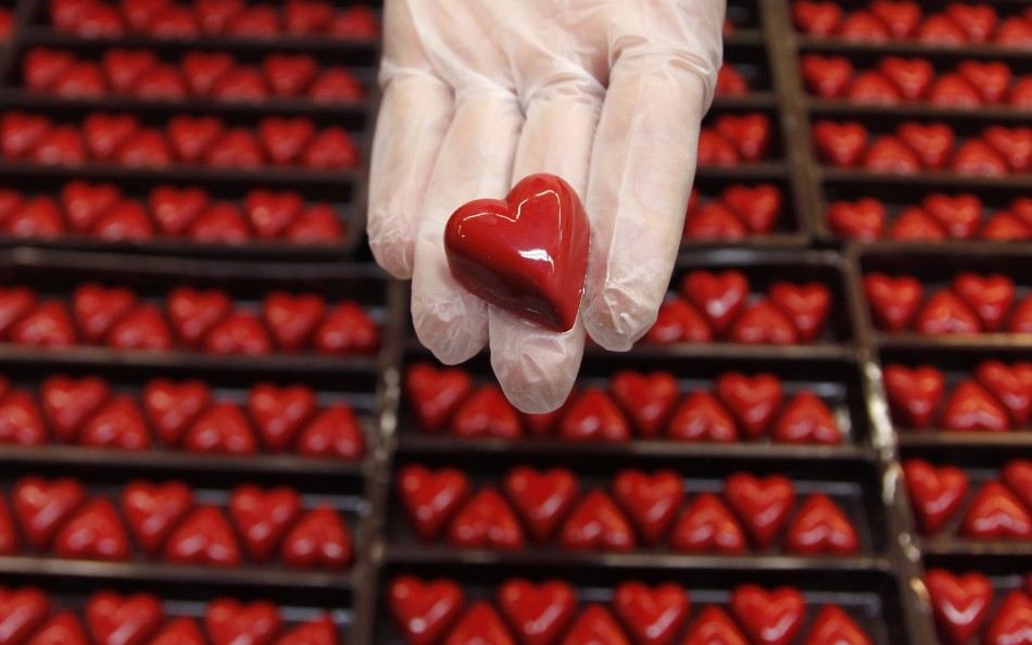 A worker displays a heart-shaped praline