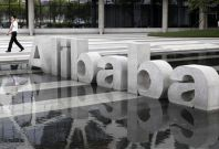A man walks past a logo of Alibaba (China) Technology Co. Ltd at its headquarters on the outskirts of Hangzhou