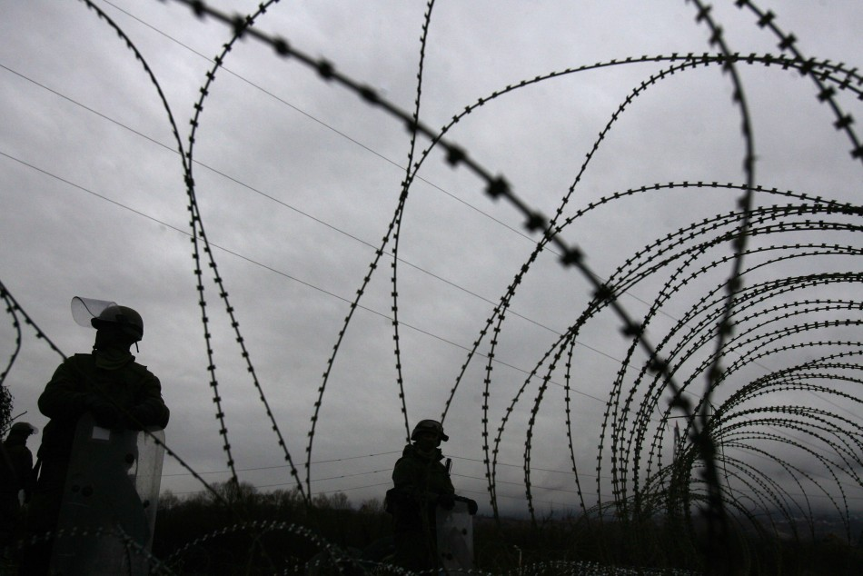 Kosovo Force (KFOR) soldiers from Germany stand guard near barbed wire along a road in the village of Jagnjenica, near Zubin Potok