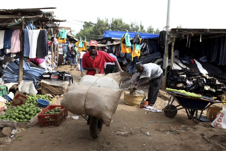 Man pushes handcart through market in Kibera, Nairobi