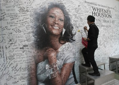 Filipino fan writes a message on a tribute wall for late American singer-actress Whitney Houston in Manila