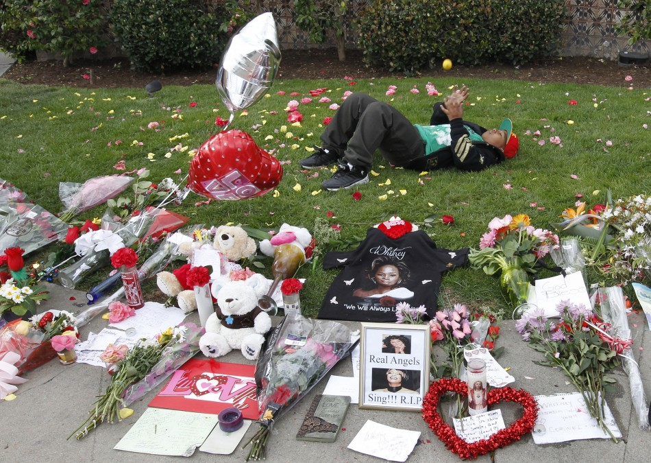Thirteen-year-old Collier lays behind a makeshift memorial to singer Whitney Houston at a corner of the Beverly Hilton Hotel