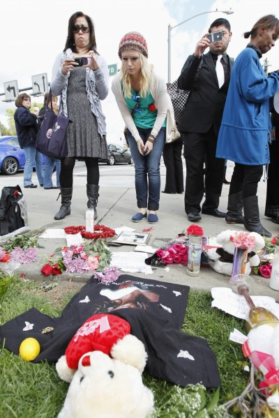 Fans gather at a makeshift memorial to singer Whitney Houston at a corner of the Beverly Hilton Hotel