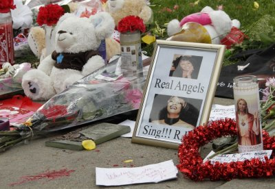Flowers, a teddy bear and photographs of the late singer Whitney Houston are pictured at a makeshift memorial to her at a corner of the Beverly Hilton Hotel
