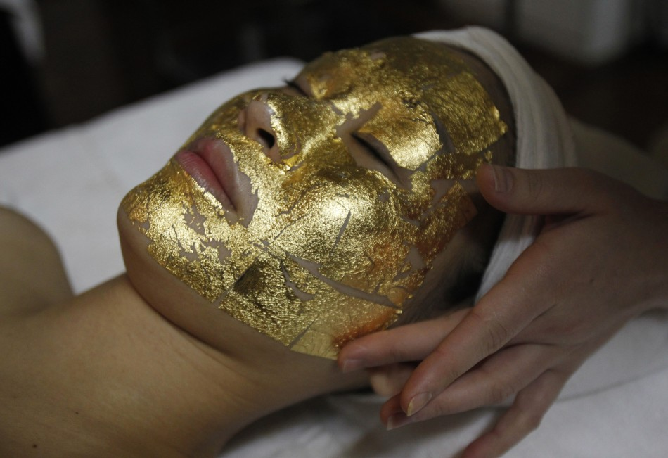 An employee pastes gold leaves onto a client039s face at the Viet My beauty salon in Hanoi