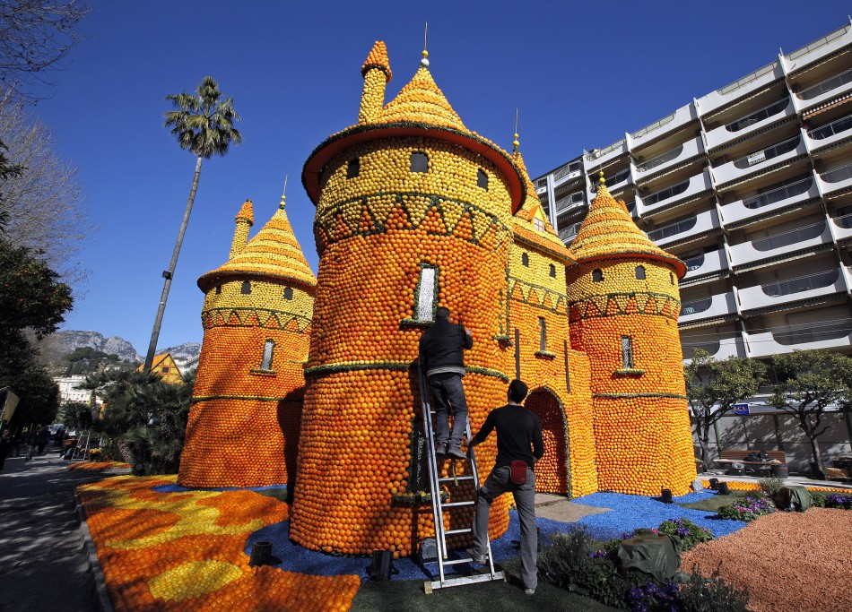 Workers put final touches to a castle made from lemons and oranges during the lemon festival in Menton