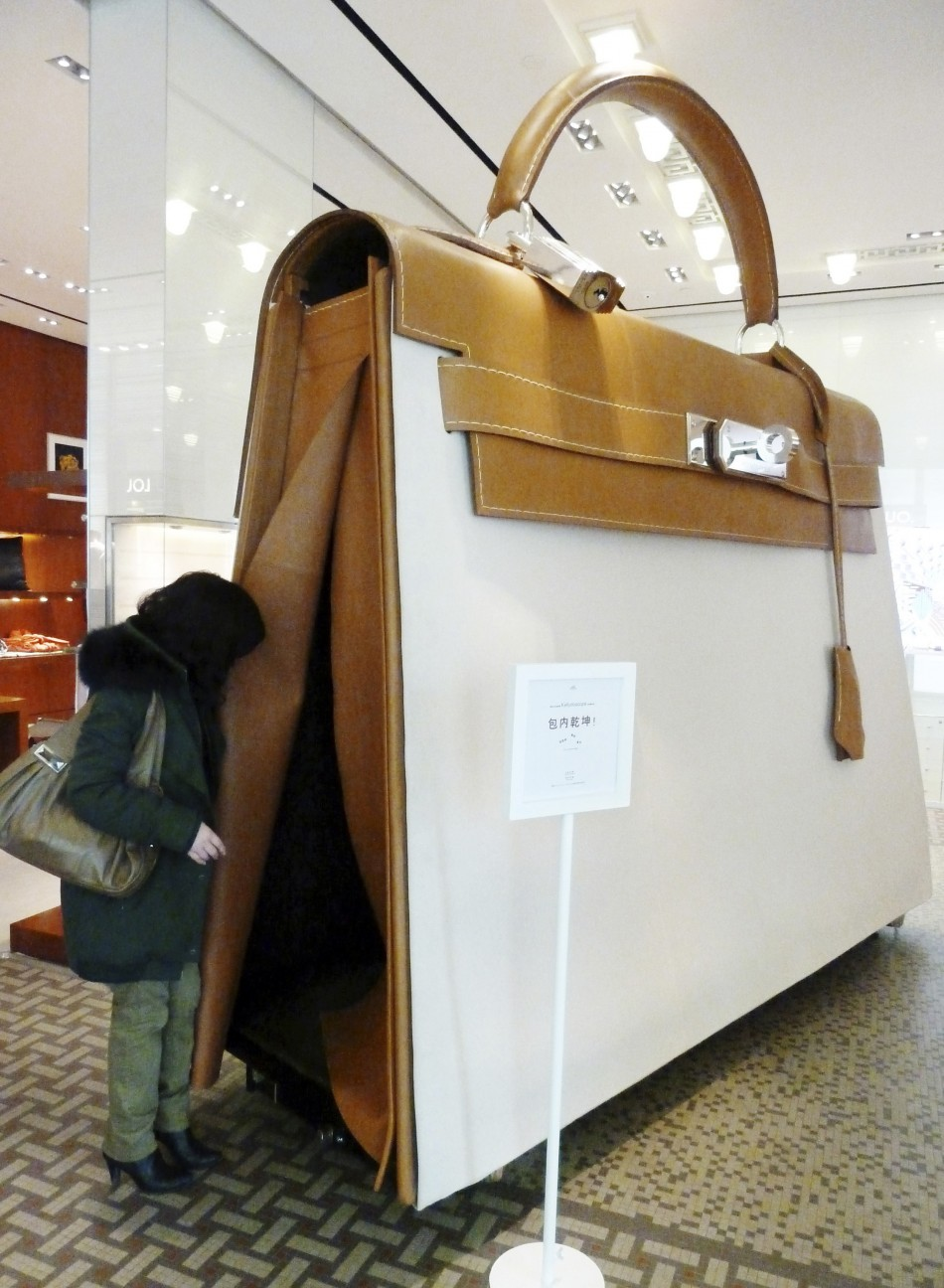 A customer looks into a giant Hermes Kelly handbag at a Hermes boutique in Nanjing