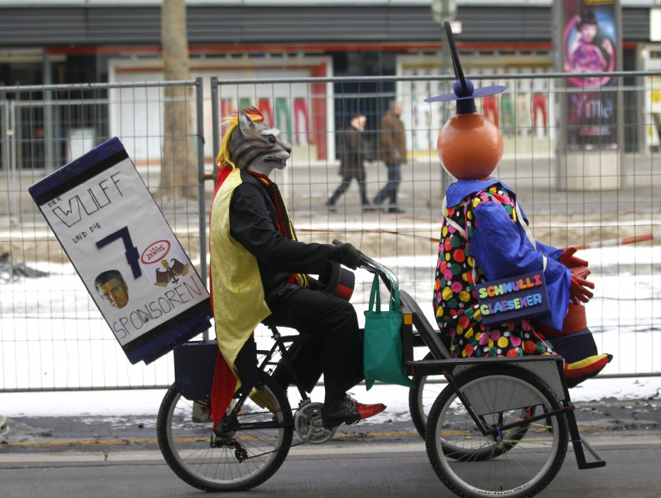 Carnival reveller in a wolf costume rides a tricycle during a carnival parade in Berlin