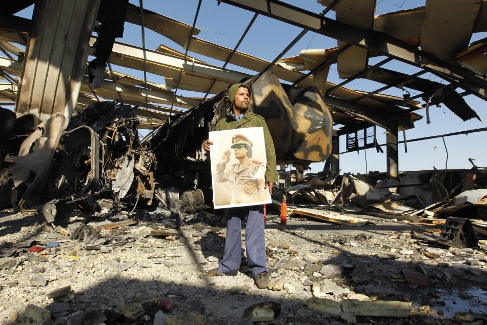 A Libyan holds a poster of Libya's leader Muammar Gaddafi