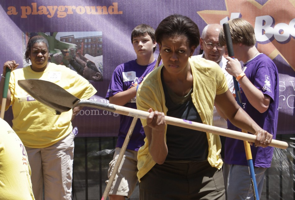 U.S. First Lady Michelle Obama holds a shovel as she joins volunteers to build a playground at Imagine Southeast Public Charter School in Washington