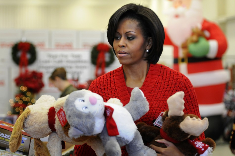 Obama carries stuffed toy animals as she helps sort toys for boys and girls as she visits the Toys for Tots distribution center at Joint Base Anacostia-Bolling in Washington