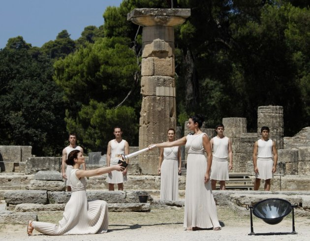 Greek actress Menegaki, playing the role of High Priestess, lights a cauldron during a ceremony in ancient Olympia