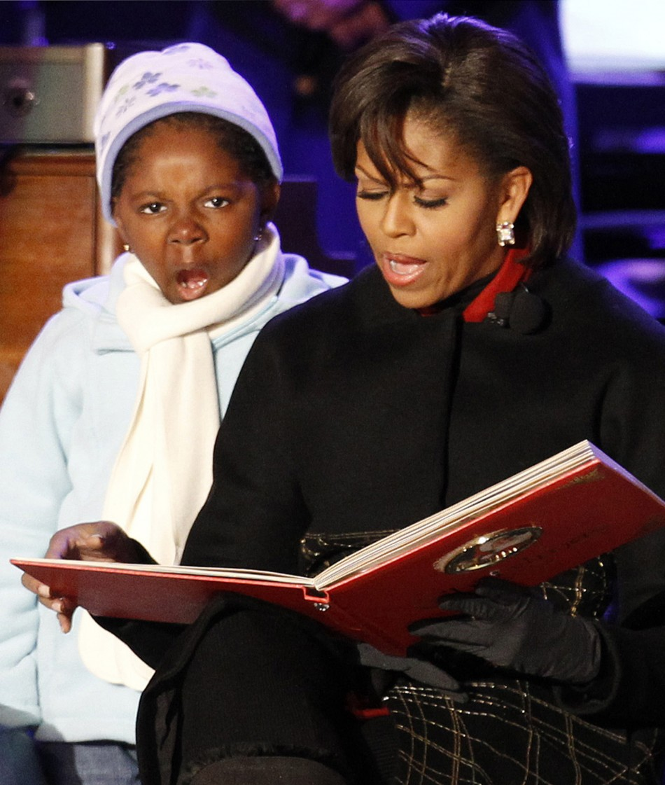 U.S. first lady Michelle Obama reads a Christmas book to children on stage during the National Christmas Tree Lighting ceremony in Washington
