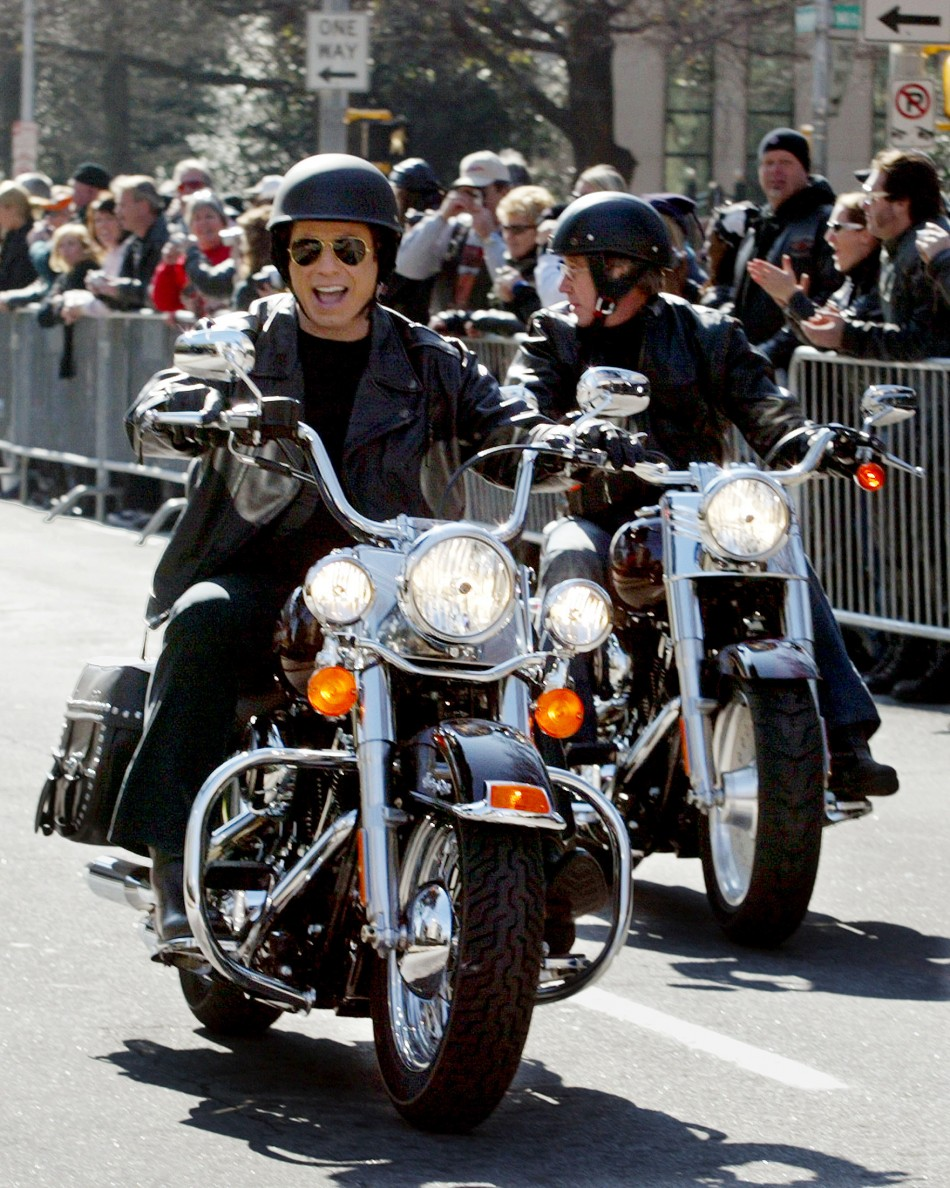 Actors John Travolta and Tim Allen (R) ride motorcycles