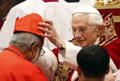 Pope Benedict XVI places a red biretta, a four-cornered hat, on the head of new Cardinal George Alencherry of India