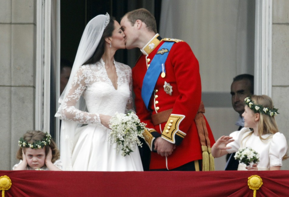 Britain's Prince William and his wife Catherine, Duchess of Cambridge, kiss as they stand next to bridesmaids Grace van Cutsem (L) and Margarita Armstrong-Jones (R) on the balcony at Buckingham Palace with other members of the Royal Family, after their we