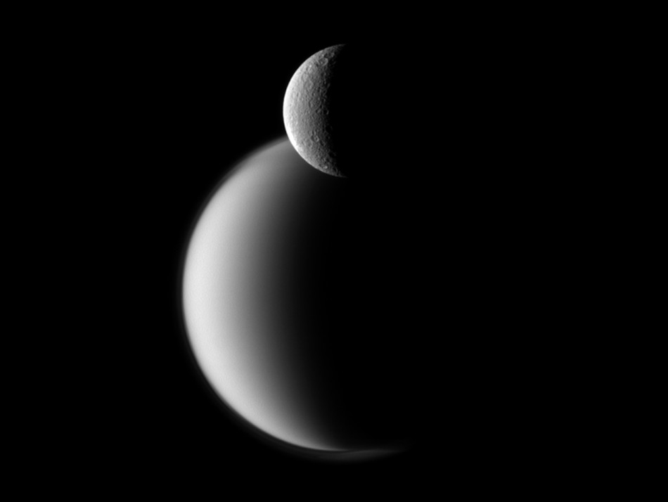 Craters appear well defined on icy Rhea in front of the hazy orb of larger Titan in this view of the two Saturn moons. NASA's Cassini spacecraft snapped the photo on Dec. 10, 2011