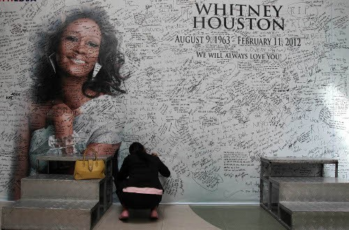 A Filipino fan writes a message on a tribute wall for the late American singer-actress Whitney Houston in Manila