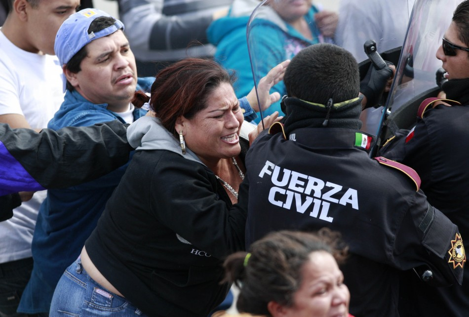 Angry relatives of inmates confront police officers outside the state prison in Apodaca