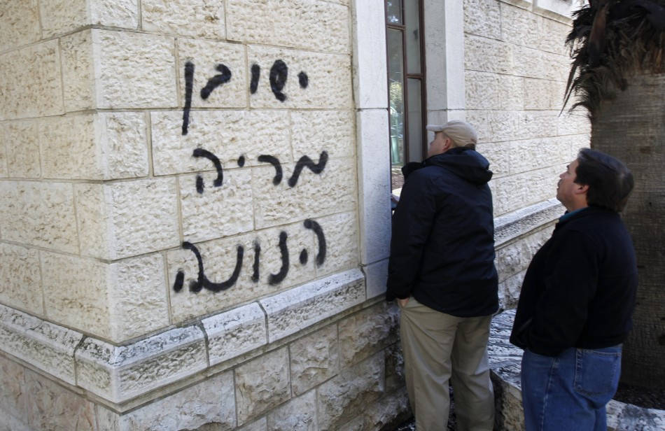 Church workers stand next to a church wall sprayed with graffiti in Jerusalem